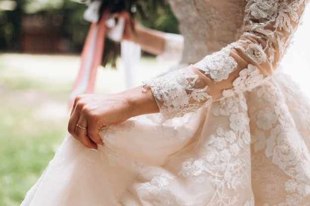 details-bridal-wedding-dress-hand-with-wedding-ring-outdoors_8353-10953