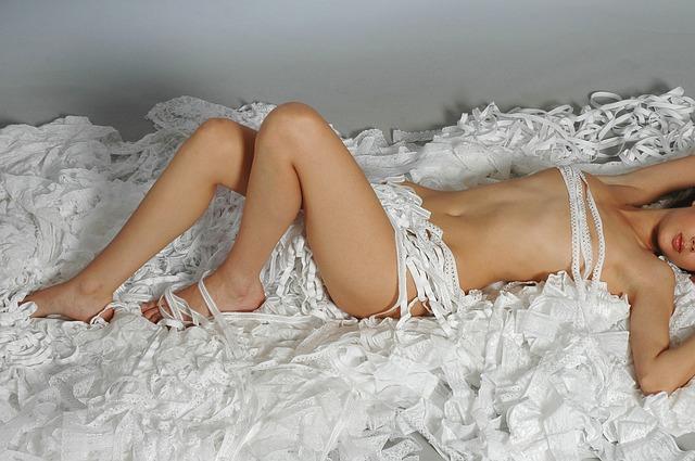 Nahá sexy Žena lež na ústrižkoch papiera, ktorými je zahalená.jpg