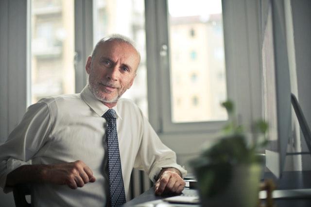 Muž v bielej košeli s modrou kravatou sedí v kancelárii a usmieva sa